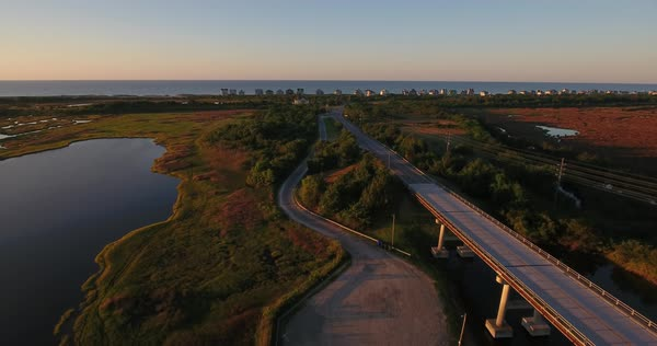 An early morning sunrise forward moving aerial establishing shot of the Topsail Island Bridge over the Intracoastal Waterway with the Atlantic Ocean in the distance.  Royalty-free stock video