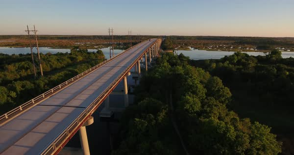 An early morning sunrise low moving forward aerial establishing shot of the Topsail Island Bridge over the Intracoastal Waterway as traffic passes over top.  Royalty-free stock video