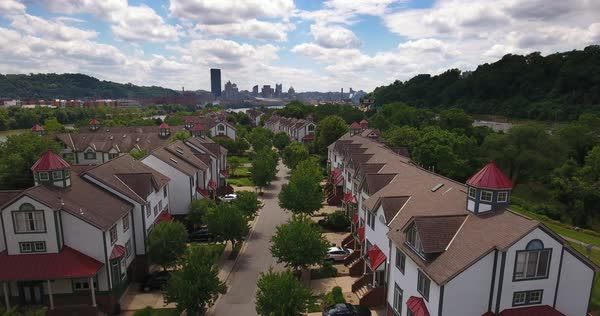 A reverse aerial establishing shot of the upscale residential homes on Washington's Landing Island with the Pittsburgh skyline in the distance.  Royalty-free stock video