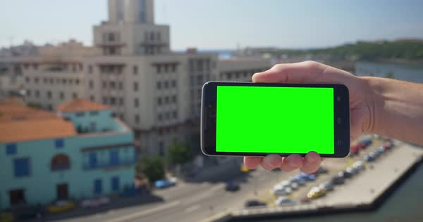 Holding a green screen smartphone in landscape mode high above the Havana, Cuba shoreline. Royalty-free stock video