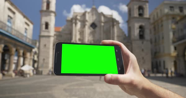 Holding a green screen smartphone in landscape mode outside Havana Cathedral Royalty-free stock video