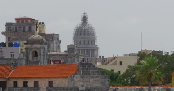 A high angle dolly establishing shot of the capitol dome covered in scaffolding in the old town section of Havana, Cuba. Royalty-free stock video