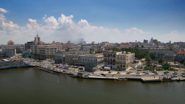An extreme wide aerial establishing shot of the Port of Havana, Cuba on a sunny summer day. Colorful vintage cars on the streets. The Capitol Dome is seen in the distance. Royalty-free stock video