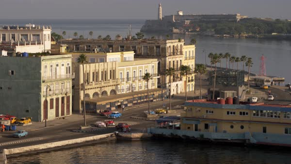 A high angle long establishing shot of the restaurants and bars along the shoreline of Havana, Cuba harbor. The lighthouse at Faro del Castillo del Morro is in the distance. Royalty-free stock video