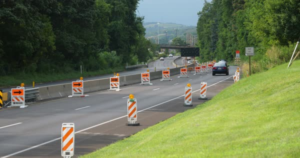 Cars navigate a closed lane in a road construction repair zone.  Royalty-free stock video