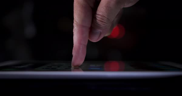 A dramatic close-up with shallow DOF of a finger pressing a button on a touchscreen tablet PC. Profile view, city traffic bokeh in the distance. Royalty-free stock video