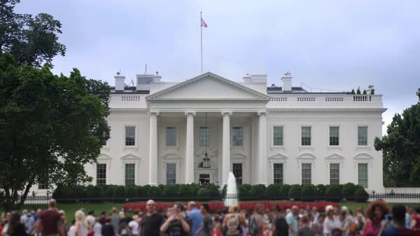 A daytime exterior establishing shot of the north side of the White House with tourists on Pennsylvania Avenue in the foreground.   Royalty-free stock video