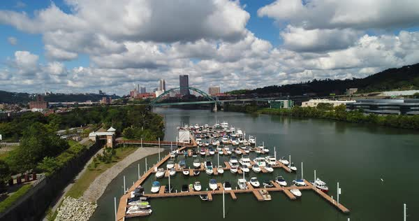 A high angle rising aerial establishing shot of a marina on the Monongahela River with the Pittsburgh skyline in the distance.   Royalty-free stock video