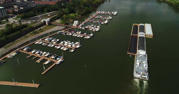 A cinematic high angle aerial flyover and tilt up shot of a marina and coal barge on the Monongahela River in Pittsburgh, PA.  Royalty-free stock video