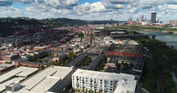 A high angle, slow moving forward aerial establishing shot of Pittsburgh's South Side business and residential district. Pittsburgh skyline in the distance.   Royalty-free stock video