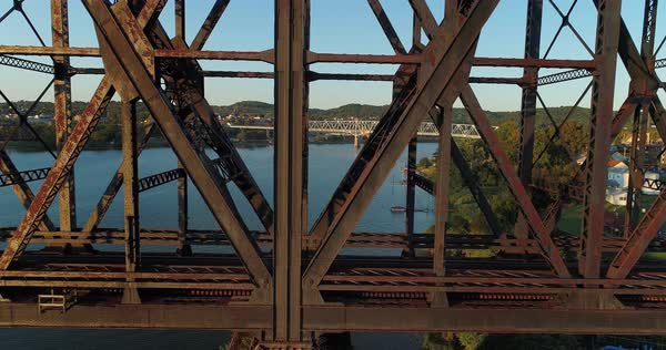 A dramatic profile aerial view of an empty, large railroad bridge spanning the Ohio River in Western Pennsylvania. The towns of Monaca and Rochester in the distance.   Royalty-free stock video