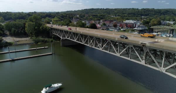 A reverse aerial view of traffic traveling on a bridge on Route 51 in Western Pennsylvania while a recreational boat passing underneath. Royalty-free stock video