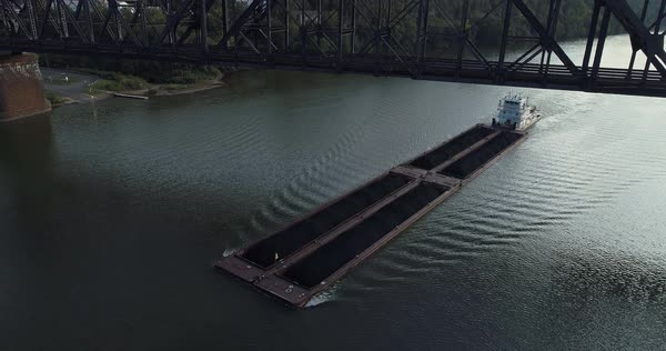 A coal barge travels on the Ohio River under a railroad trestle bridge.   Royalty-free stock video