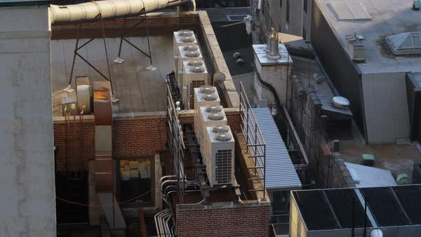 Daytime high angle view of running air conditioner units atop buildings in Manhattan.  Royalty-free stock video