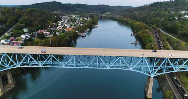 A daytime aerial profile establishing shot of the Rt 40 Market Street Bridge over the Monongahela River in Brownsville, PA - a Pittsburgh suburb.   Royalty-free stock video