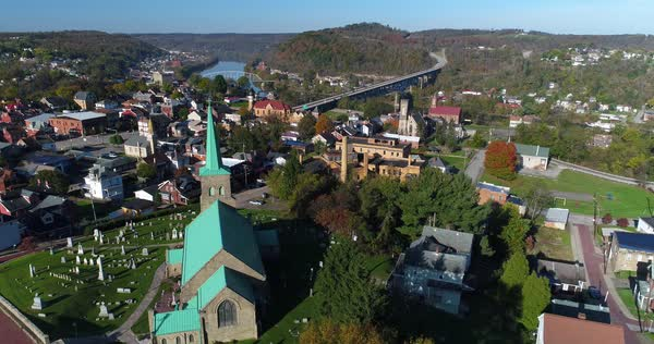 A morning high angle forward aerial establishing shot of the small town of Brownsville, PA - a Pittsburgh suburb. Bridges over the Monongahela River in the distance.  Royalty-free stock video