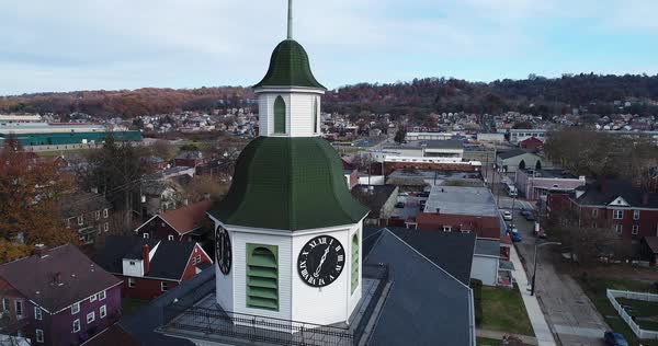 A slow push in aerial establishing shot of a church's steeple in a small American town during the late Autumn.   Royalty-free stock video
