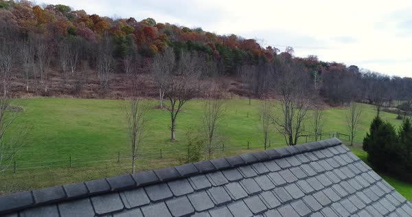 A slow reverse aerial view revealing a farmhouse's roof and shingles.   Royalty-free stock video