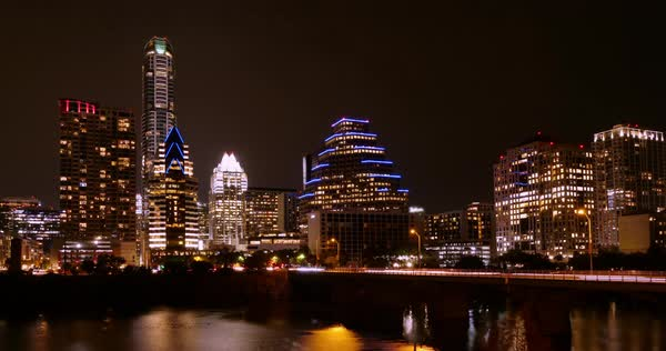 A night timelapse view of the Austin city skyline with the Colorado River in the foreground.   Royalty-free stock video
