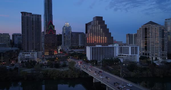 A slow, lowering aerial evening establishing shot of the Austin city skyline and traffic on the S Congress Avenue Bridge.   Royalty-free stock video