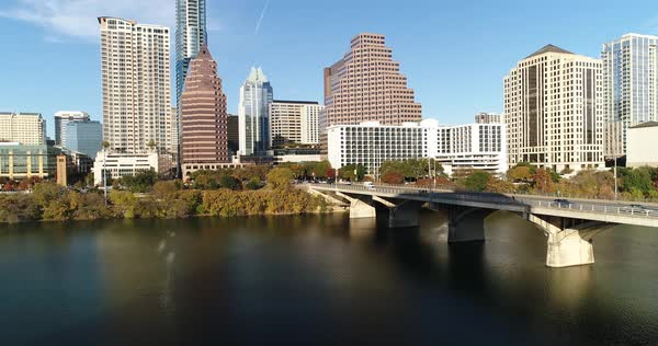 A slow forward low aerial view of traffic flowing over the S Congress Avenue Bridge over the Colorado River in downtown Austin, Texas on an early autumn evening.  Royalty-free stock video