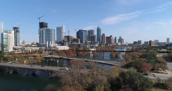 A slow rising aerial establishing shot (DX) of the Austin city skyline with the Pfluger Pedestrian Bridge and Lamar Boulevard Bridge in the foreground on a late sunny Autumn day.   Royalty-free stock video