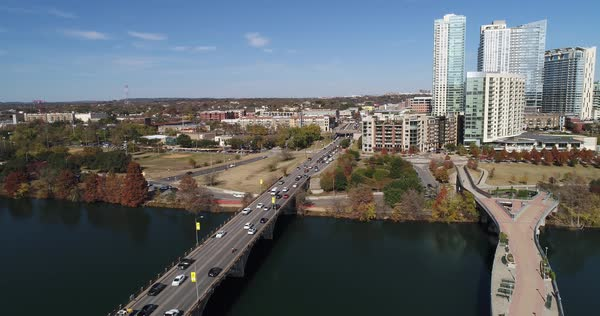 A slow forward aerial establishing shot (DX) of the Austin city skyline with the Pfluger Pedestrian Bridge and Lamar Boulevard Bridge in the foreground on a late sunny Autumn day.   Royalty-free stock video