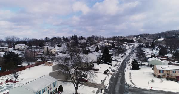 A daytime winter overcast aerial establishing shot of a typical Western Pennsylvania residential neighborhood. Slow forward motion. Snow covered roofs, houses, and yards. Pittsburgh suburbs.   Royalty-free stock video
