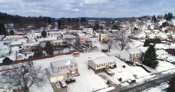 A daytime winter overcast aerial establishing shot of a typical Western Pennsylvania residential neighborhood and intersection. Slow forward motion. Snow covered roofs, houses, and yards. Pittsburgh suburbs.   Royalty-free stock video