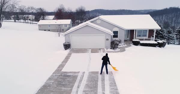 A low angle aerial view of a homeowner shoveling snow from the driveway at a home in a typical Pennsylvania neighborhood. Pittsburgh suburbs.   Royalty-free stock video