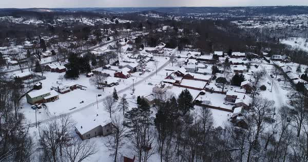A high angle aerial slow push forward establishing shot of a typical Pennsylvania residential neighborhood on a cold overcast winter's day. Pittsburgh suburb.  Royalty-free stock video