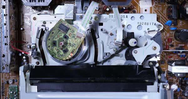 A closeup inside view of the electronics of a VCR as a VHS tape is ejected. Tape gets stuck and krinkled. Top off view. With audio.  Royalty-free stock video