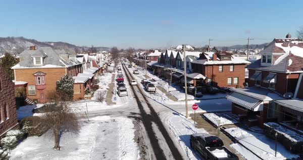A daytime winter reverse aerial establishing shot of a quiet small town's residential neighborhood after a fresh snowfall. Pittsburgh suburbs.   Royalty-free stock video