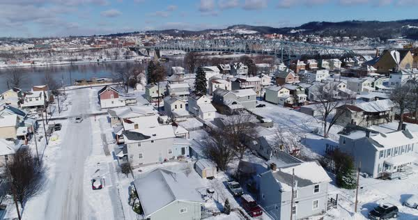 A slow rising forward winter aerial establishing shot of snow covered roads and houses in a rust belt residential neighborhood. Rochester and Ohio River in the distance. Pittsburgh suburbs.   Royalty-free stock video