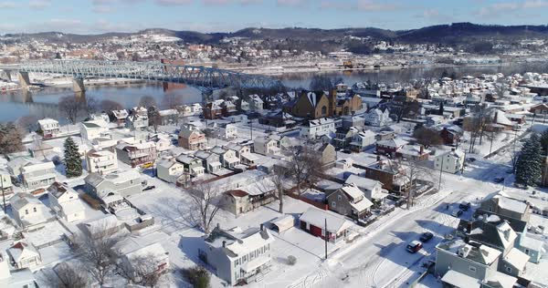 A slow reverse winter aerial establishing shot of snow covered roads and homes in a rust belt residential neighborhood. Rochester and Ohio River in the distance. Pittsburgh suburbs.   Royalty-free stock video