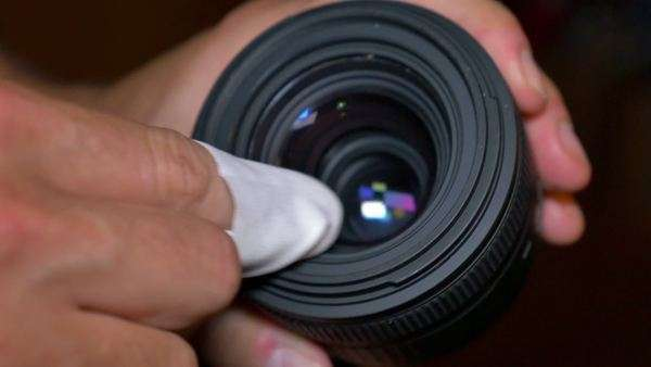 A photographer cleans his camera lens with a soft cloth. Royalty-free stock video