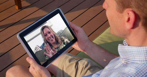 An over the shoulder shot of a man video chatting on his tablet PC outside. Screen image customizable upon request. Royalty-free stock video