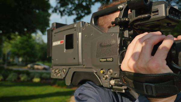 A close-up shot of a cameraman focusing a shoulder-mounted camera. Royalty-free stock video