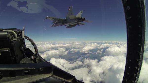 POV from backseat of F18 fighter plane flying and holding position as other F18 plane maneuvers over top and to the side, very close and holds that position as they move through clouds. Royalty-free stock video