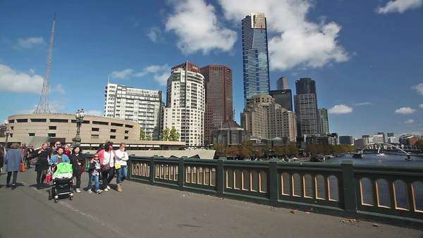 Melbourne, Australia - April 2, 2015: People walking across the Princes Bridge in Melbourne, Australia, with iconic buildings in the background Royalty-free stock video