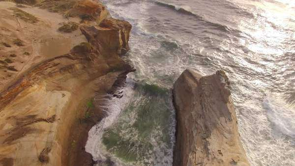 Bird's eye view of sea stack along Cape Kiwanda on the Oregon coast. Rights-managed stock video