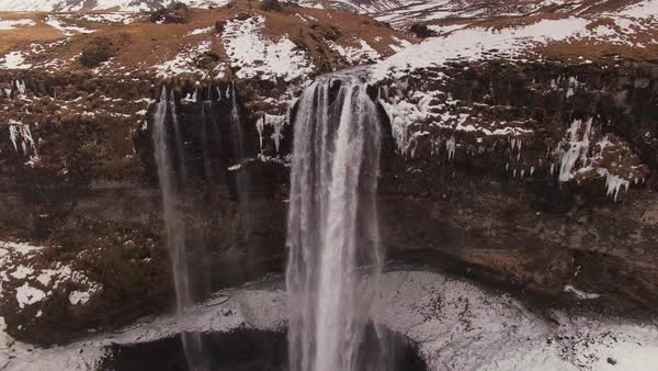 Aerial pan down over Seljalandsfoss waterfall in Iceland.  Rights-managed stock video