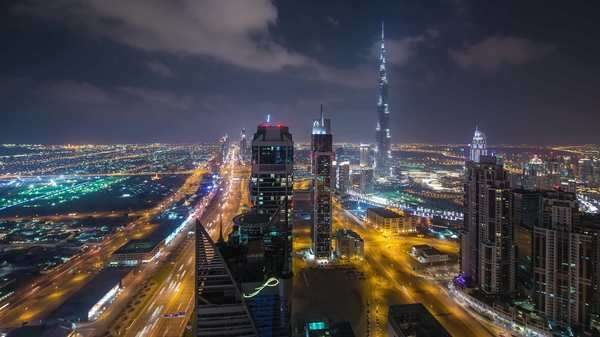 Static timelapse busy downtown Dubai  Cityscape at night with Burj Khalifa. Rights-managed stock video