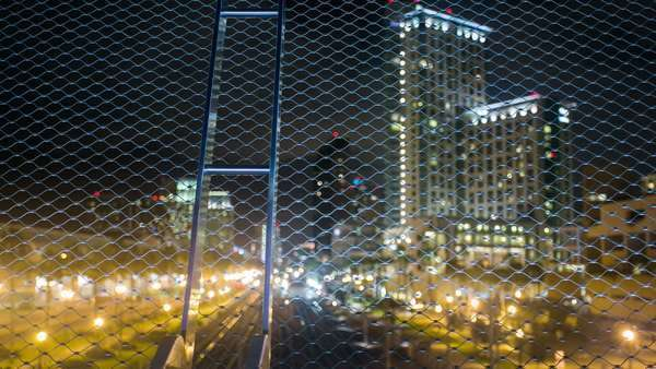 Timelapse dolly shot of San Diego Downtown bokeh fence with city at night. Rights-managed stock video