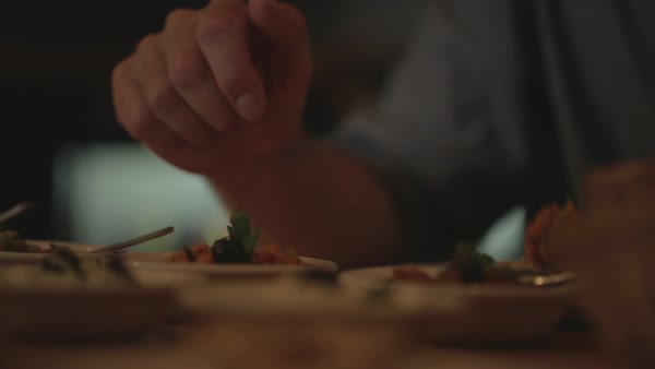 Hand-held shot of a person scooping food from a plate into another plate Royalty-free stock video