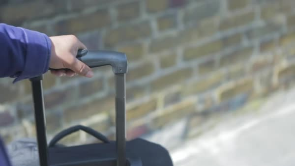 Hand-held shot of a person pushing a rolling suitcase Royalty-free stock video