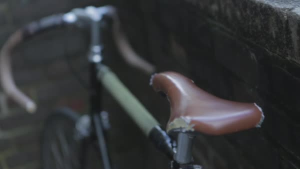 Hand-held shot of a road bike parked against a brick wall Royalty-free stock video