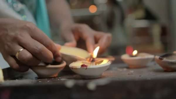 A slow motion shot of an Indian woman lighting a candle to pray in Hindu temple. Royalty-free stock video