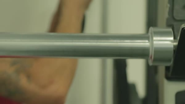 Hand-held shot of a man taking a weight plate off a barbell Royalty-free stock video