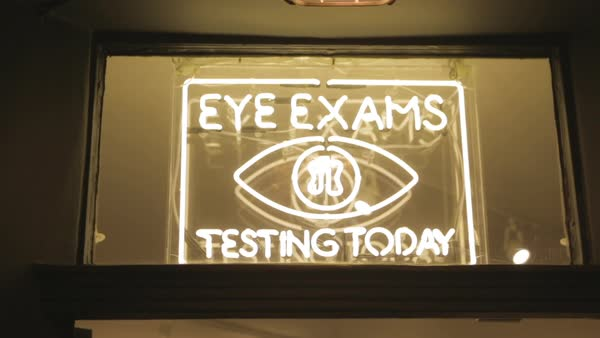 Hand-held shot of a neon sign advertising eye exams Royalty-free stock video